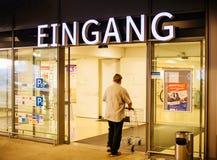 Homem com o carrinho de compras que enetering a loja de Edeka sob o entra de Eingang Imagem de Stock