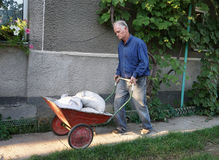 Homem com o carrinho de mão completo de sacos do cimento Imagens de Stock