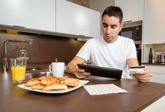 Homem com o cartão de crédito de revisão da tabuleta eletrônica Imagens de Stock