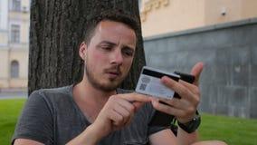 Homem com o cartão de crédito durante a compra através do Internet usando o telefone esperto no parque que senta-se sob uma árvor video estoque
