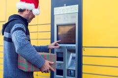 Homem com o cliente do chapéu do Natal que usa o cargo automatizado do serviço do auto imagem de stock