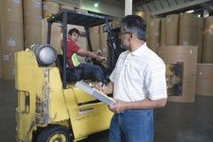 Homem com o colega na trilha da empilhadeira na fábrica Foto de Stock Royalty Free