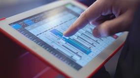 Homem com o console de mistura no som da verificação da tabuleta no conceito do evento, da música, da tecnologia, dos povos e do  filme