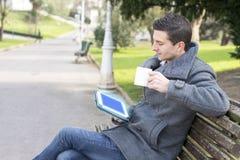 Homem com o copo do tablet pc e de café que senta-se no banco de madeira, o imagem de stock