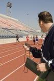 Homem com o cronômetro que olha a competência dos atletas foto de stock