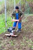 Homem com o cultivador do motor de encontro ao tempo de mola Imagens de Stock Royalty Free