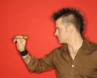 Homem com o dardo de jogo do mohawk. Imagens de Stock