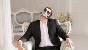 Homem com o esqueleto da composi??o que senta-se na cadeira, e assustador olhando a c?mera video estoque