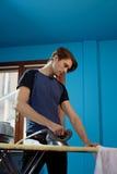 Homem com o ferro que faz tarefas Imagens de Stock