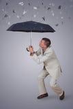 Homem com o guarda-chuva sob a moeda da chuva Imagens de Stock Royalty Free
