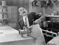 Homem com o laço colado na picadora de carne fotografia de stock royalty free