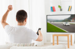 Homem com o motorsports de observação remoto na tevê em casa fotos de stock royalty free