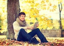 Homem com o PC da tabuleta no parque do outono fotos de stock