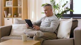Homem com o PC da tabuleta que senta-se no sofá em casa video estoque