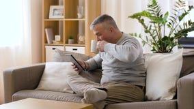 Homem com o PC da tabuleta que senta-se no sofá em casa filme