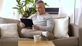 Homem com o PC da tabuleta que senta-se no sofá em casa vídeos de arquivo