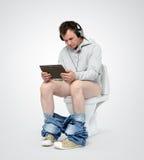 Homem com o PC e os fones de ouvido da tabuleta que sentam-se no toalete Foto de Stock