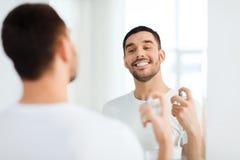 Homem com o perfume que olha ao espelho no banheiro Fotos de Stock Royalty Free