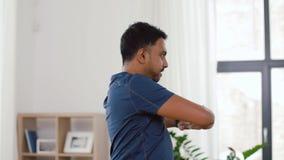 Homem com o perseguidor da aptidão que estica a cintura em casa video estoque