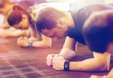 Homem com o perseguidor da coração-taxa que exercita no gym Fotografia de Stock