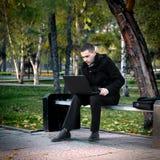 Homem com o portátil ao ar livre fotos de stock royalty free