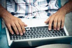 Homem com o portátil em seu regaço que trabalha o tiro exterior em linha fotografia de stock royalty free