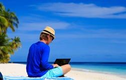 Homem com o portátil na praia tropical Foto de Stock