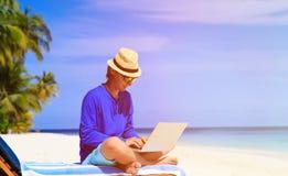 Homem com o portátil na praia tropical Fotografia de Stock