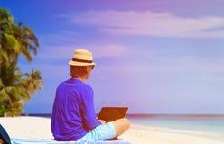 Homem com o portátil na praia tropical Imagens de Stock