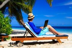 Homem com o portátil na praia tropical Foto de Stock Royalty Free