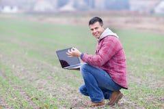 Homem com o portátil no campo Fotografia de Stock Royalty Free