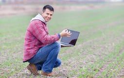 Homem com o portátil no campo Foto de Stock