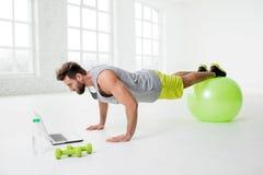 Homem com o portátil no gym imagens de stock