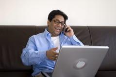 Homem com o portátil no telefone fotografia de stock royalty free