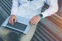 Homem com o portátil que senta-se no banco fora imagens de stock royalty free