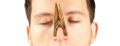 Homem com o pregador de roupa no nariz isolado no fundo branco imagem de stock