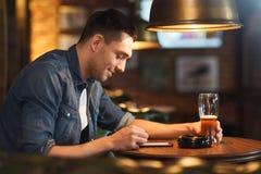 Homem com o smartphone e a cerveja que texting na barra Fotografia de Stock