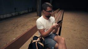 Homem com o smartphone na noite na cidade filme