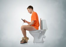 Homem com o smartphone que senta-se no toalete fotos de stock royalty free