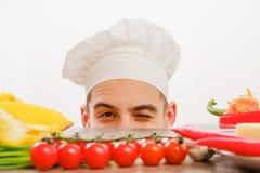 Homem com o tampão do cozinheiro no fundo branco Cozinheiro chefe com os vegetais na tabela Cozinheiro com a cara alegre no fim d imagens de stock