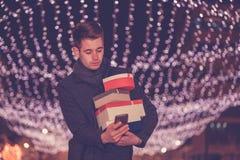 Homem com o telefone celular, guardando presentes na rua foto de stock royalty free