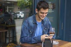 Homem com o telefone celular na barra Fotografia de Stock