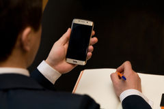 Homem com o telefone celular que senta-se em uma tabela que trabalha em seu caderno Fotos de Stock Royalty Free