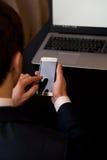 Homem com o telefone celular que senta-se em uma tabela que trabalha em seu laptop Fotografia de Stock