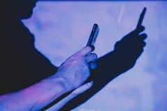 Homem com o telefone esperto nas mãos foto de stock