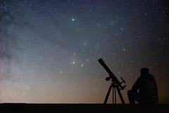 Homem com o telescópio da astronomia que olha as estrelas fotografia de stock