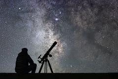 Homem com o telescópio da astronomia que olha as estrelas Fotografia de Stock Royalty Free