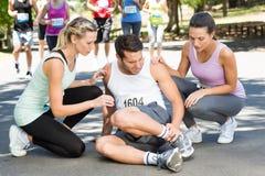 Homem com o tornozelo ferido durante a raça no parque foto de stock royalty free