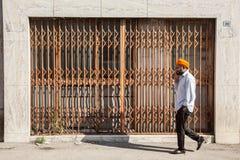 Homem com o turbante alaranjado na frente da loja shuttered Foto de Stock Royalty Free