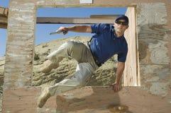Homem com obstáculo de salto da arma da mão na escala de acendimento Imagens de Stock